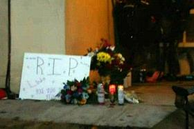 SHOOTING: (Above) Candles and flowers left at the door.