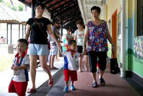 ANXIOUS: Madam Angela Lim (in black top) taking her son to school.