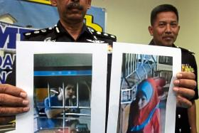 Malaysian police holding up photographs of the suspect in men's clothing (left) and in women's clothing (right).