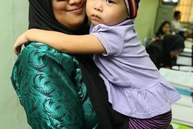 NEW FAMILY: Mrs Cannie Wong said she completed the adoption process for Angie (above, with a Johor social worker) in Malaysia.