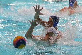 GULF IN STANDARDS: A water polo player from Slovakia's KVP U-18 team (in blue cap) helping his team to a 12-4 win over Singapore Under-23 at the Toa Payoh Swimming Complex yesterday.