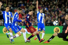 Barcelona forward Lionel Messi attempts to score a goal past Espanyol goalkeeper Pau Lopez.