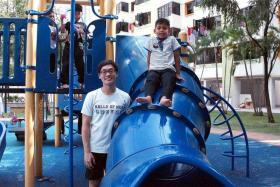 VOLUNTEER: Mr Ivan Neo, a recipient of the GIC Sparks & Smiles Award, helped mentor six-year-old Muhammad Nursyafiq Fathullah Jasumah (striped shirt).