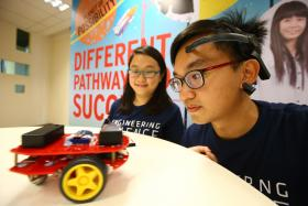 MIND POWER: Engineering Science students Max Pang Ek Wee and Kimberlyn Loh Cheng Lin with their mind-controlled robot.