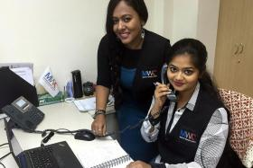 MULTILINGUAL: (From left) Ms Kavitha Rajoo and Ms Reshma Basu speak to callers in their native language.