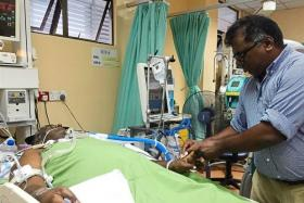 Wilson Ramamoorthy wiping the sweat off his brother Sundaraj, who has been in a coma at the Tengku Ampuan Afzan Hospital's ICU ward after an accident last month.