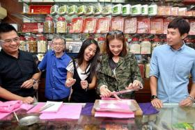 CELEB STUDENTS: (Above) Tan, Belinda Lee (in black) and Dawn Yeoh (in green) learning about all things TCM, such as how to wrap Chinese herbs  at Tong Keow Medical Hall.