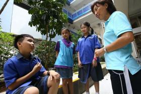 SMART: (Above) Principal of West Spring Primary School, Mrs Jacinta Lim, talking to pupils in their new collared uniform, which was designed by Miss Tiffany Ng and Miss Ho Bao Yiing.
