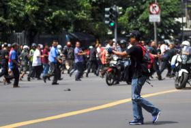 A gunman points his weapon on the street during attacks in the Indonesian capital Jakarta on January 14, 2016.