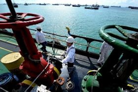 PROCESS: Port chemist Gary Lim prepares to board a boat at Marina South Pier, he uses a rope ladder to board oil tanker MV Murray, he inspects the pipes of MV Murray (above).