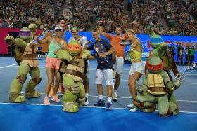 "TURTLE POWER: (From left) Teenage Mutant Ninja Turtles characters posing with Caroline Wozniacki, Milos Raonic, Roger Federer, Lleyton Hewitt, Novak Djokovic and Victoria Azarenka during the Australian Open's ""Kids Day"" on Saturday."