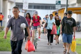 EXPERIMENT: TNP reporter Elizabeth Law (on bicycle) finds the shared path under the MRT tracks in Tampines wide enough for pedestrians and cyclists to share.
