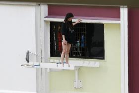 1: The woman looked weak as she took turns standing, sitting and squatting on the laundry rack on the sixth storey.