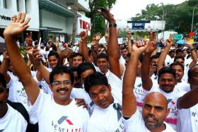 HARMONY: Foreign workers from Westlite Dormitory waving to the camera during the SG50 Jubilee Big Walk last November.