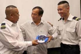 LIFESAVERS: Mr Khoo Teng Guang (middle), holding an AED and thanking senior security officers Mr Hasan Ahmad (far left) and Mr Javerson Chok for saving his life.