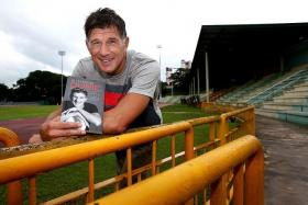 DOWN MEMORY LANE: Aleksandar Duric showing a copy of his autobiography, Beyond Borders, at Queenstown Stadium, where his Singapore adventure began 17 years ago.