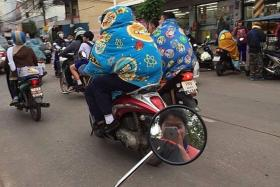 BRRR: Motorcyclists bundled up in colourful blankets while riding.