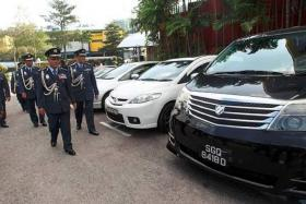 SMUGGLED CARS: Johor State Customs director Datuk Ramli Johari (second from right) and fellow Customs officials inspecting the seized vehicles.