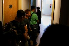PATIENT: CNB officers waiting to enter a room whose occupants have been flagged. A hotel employee would ring the doorbell and wait for the door to be opened before the officers can enter to conduct checks.
