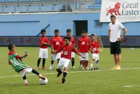 RIGHT FIT: Aleksandar Duric (far right) conducting a kids' football clinic last year as part of Great Eastern's SG50 Wishes campaign.