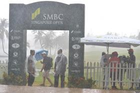 UNDERCOVER: Spectators and officials braving the rain at Serapong, as thunderstorms hit the tournament for the third time in four days.