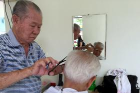 Mr Goh Kow Hoon, giving a haircut to a senior citizen at Paya Leber Wellness Centre. He has been volunteering his services as a barber since 2010