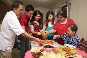 UNITED: Madam Dolly Tan (second from right), tossing yusheng with her family and Ms Cess (in red-black dress) and Mr Anton (in red shirt).