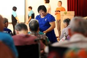 FESTIVE CHEER: Ms Irene Lee (in blue) raised enough money to purchase 1,000 pyjamas for the elderly residents of Man Fut Tong Nursing Home this Chinese New Year.