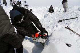 DEADLY: A rescuer cutting through ice during the search for survivors after a deadly avalanche on the Siachen glacier in Kashmir.