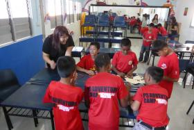 HELPING HAND: Ms Maggie Chia (in black) teaching the children of Yayasan Radmila Children's Home in Batam to make Chinese New Year crafts.