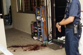 BLOODY: A policeman stands near the bloodstains outside the HDB unit where the maid works.