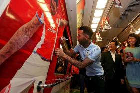 STAR POWER: SMRT's Dawn Low (above) and FAS vice-president Lim Kia Tong watching as Jermaine Pennant signs his name on his poster emblazoned inside a train carriage.