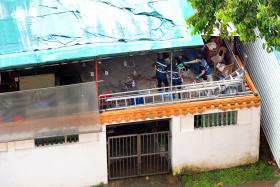 Police at the scene where former temple medium Tan Poh Huat, 53, was found lying motionless in a pool of blood outside the prayer hall of Chua Chu Kang Lian Sing Keng temple on Teck Whye Lane.