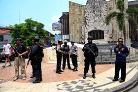 ALERT: Indonesian police standing in front of the monument dedicated to victims killed in the 2002 Bali bombing by Jemaah Islamiah, which is seeing a resurgence.