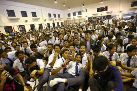 MUSIC IDOLS: Nathan Hartono and Charlie Lim posing with students at Canberra Secondary School (above) and performing for the crowd.