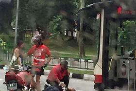 HELP: A bus driver crouching over the boy. A couple on a motorcycle stopped to assist the boy.