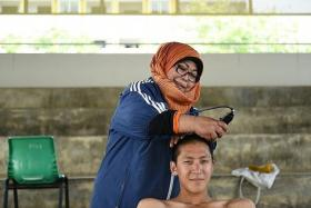 TEKONG BARBER: Madam Rose Sadiah shaving the heads of recruits, a job she says requires speed and efficiency.