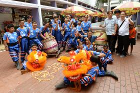 FRIENDS: Norahimah Haja, Chua Tian Yi and Muhd Fitri Mohd Noor are part of a volunteer lion dance troupe (above) made up of teenagers from different races.