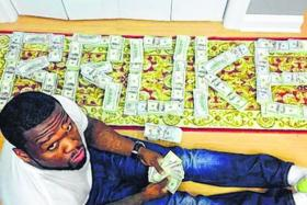 "BOLD: 50 Cent with bundles of cash arranged to spell the word ""broke""."