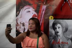 FAN: A Madonna fan in the Philippines taking a selfie in front of a poster of the 57-year-old pop diva, who will perform her second show in Manila today.