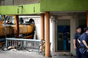 TOPPLED: The mobile construction crane crashed through the wall of a POSB branch at Block 2A, Woodlands Centre