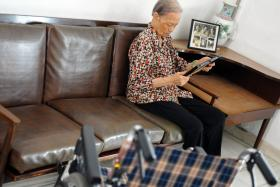 Loving: (Above) Madam Leong Suet Ching looking at old photographs of her and her sister, Madam Leong Suet Ying.