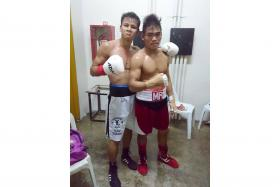 THERE'S ALWAYS A FIRST TIME: Singapore boxer Ridhwan Ahmad (in white trunks) posing with his beaten opponent, Melchor Roda, who suffered his first pro career defeat.