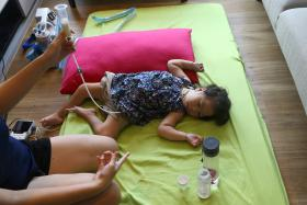 WEAK: Madam Jasmine Lim feeding Sarah through a tube in her stomach as she is unable to swallow.