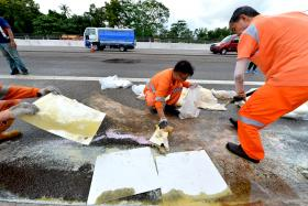 The clean-up crew removing the spilled oil by the side of Bukit Timah Expressway on Jan 29.