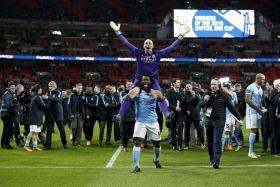 CHAMPIONS: Wilfried Bony (below) lifts penalty shoot-out hero Willy Caballero after Manchester City win the League Cup.