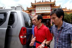 Loh Suan Lit (in red) was brought back to Chin Long Kong Temple where he allegedly murdered Mr Tan Poh Huat.