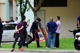 HUNT: (Above) During the search, police officers took away two packages believed to contain a hairpin and a pillow (circled) belonging to Miss Tan, according to Lianhe Wanbao. Police anti-riot vehicles were seen at the scene. Miss Tan was eventually found crying at the void deck of Block 152, Rivervale Crescent.