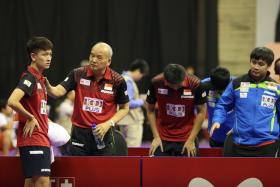 OUT: Men's national coach Liu Jiayi (second from far left), talks to Clarence Chew during Singapore's 3-1 defeat by Ukraine in the team's final Group C tie yesterday. Liu has dubbed Chew Singapore's future No. 1 male paddler.