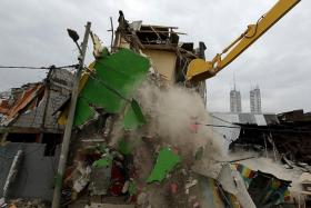DEMOLISHED: (Above) Bulldozers knock down buildings in Kalijodo red-light district of Jakarta, Indonesia, on Feb 29 as part of a nationwide effort to eradicate prostitution.